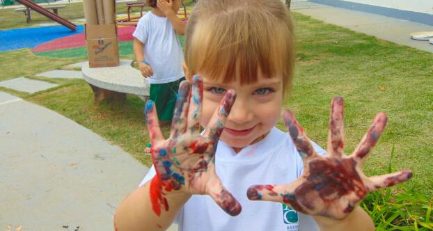 Imagem de menina com as mãos sujas de tinta.
