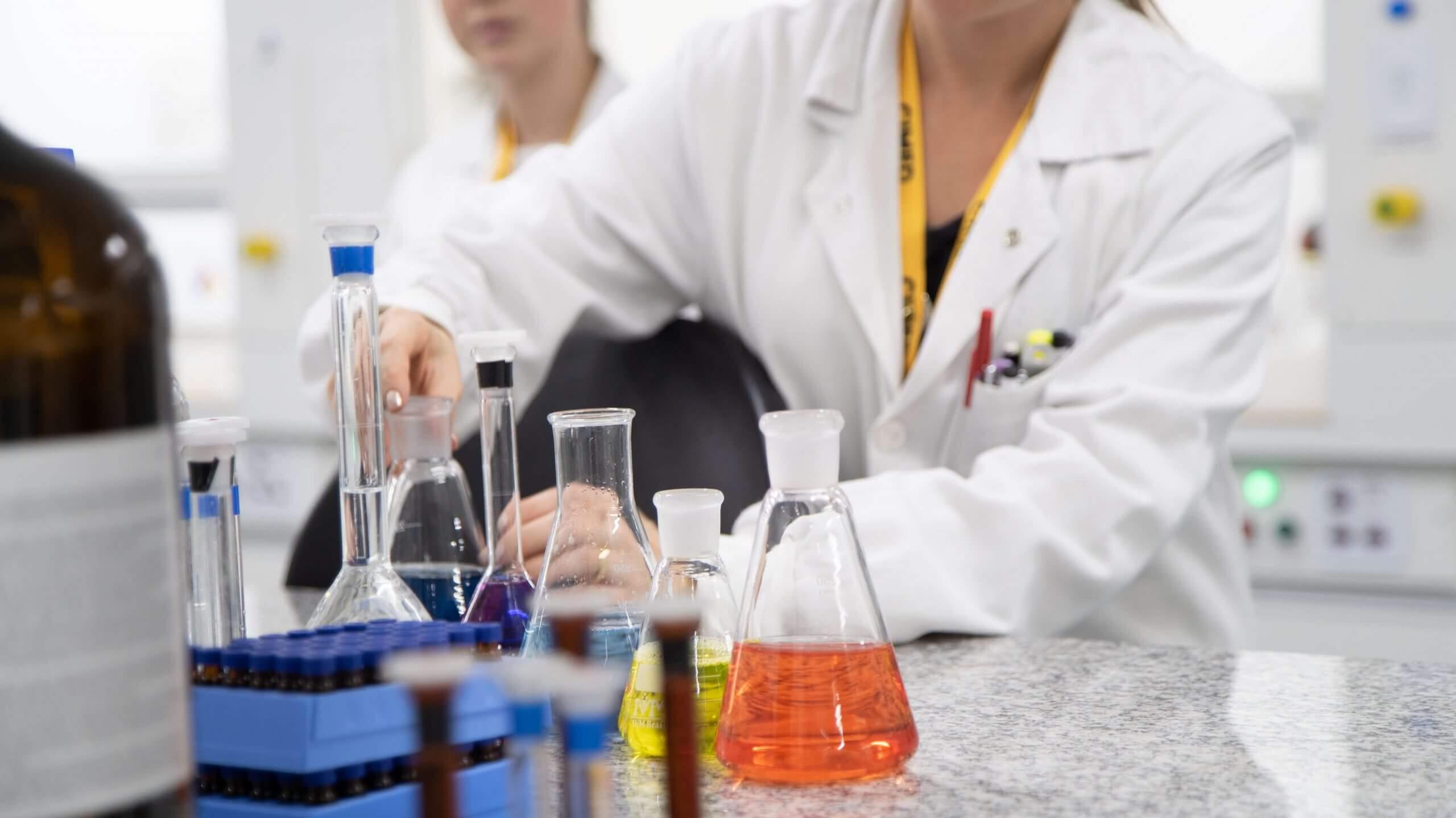 Imagem de mulher manipulando frascos em laboratório.