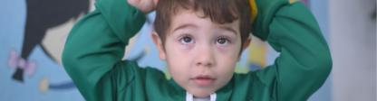 Imagem de menino com chapéu amarelo.